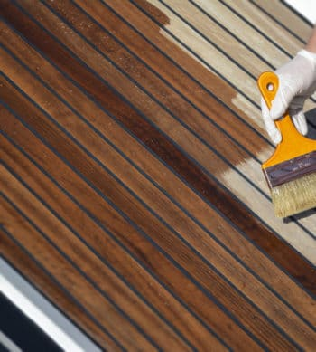 Deks Olje D1 being applied to a boat deck with a brush
