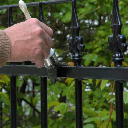 Black Owatrol Deco being applied to metal gate with a brush