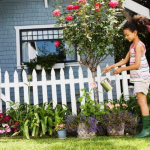 Girl watering plants by a picket fence