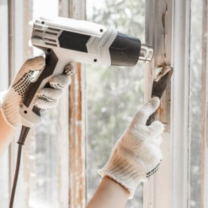 heat gun and scraper being used to remove paint from window frame