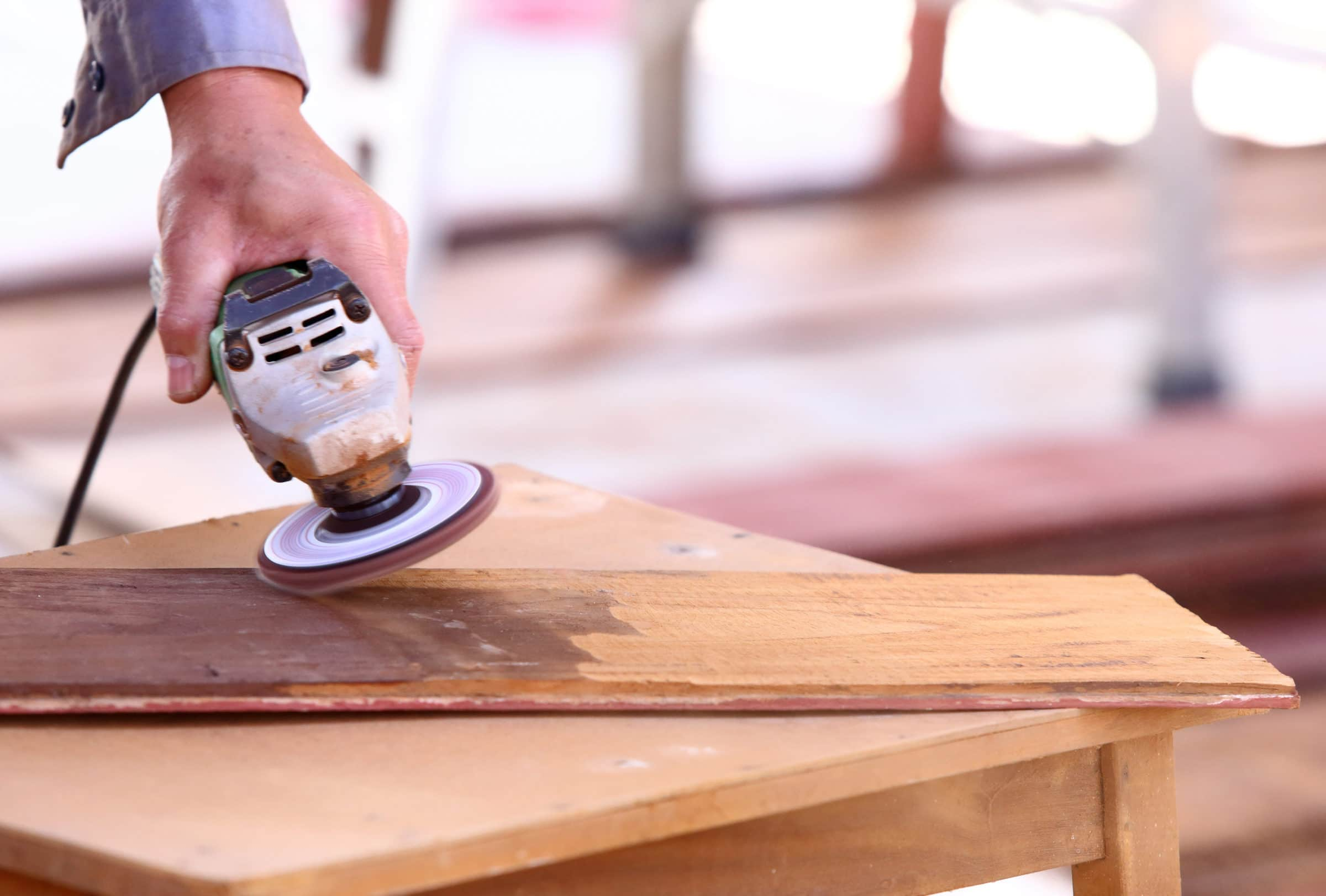 Electric sander being used to remove paint from wood