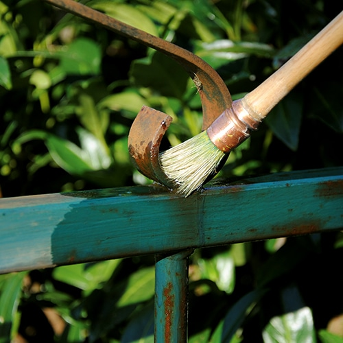 Owatrol oil being applied to a rusted metal fence